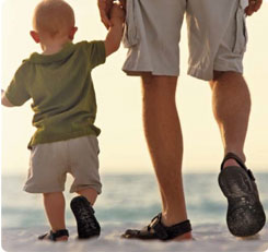 father and son walking along a beach